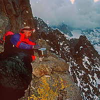 Mountaineer John Moynier prepares to cook a meal during a bivouac near the summit of Temple Crag in the Palisade Glacier region of California's Sierra Nevada.
