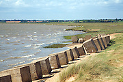 Strong winds create waves causing erosion to saltings River Deben from Bawdsey looking upstream, Suffolk, England. The coincrete blocks in the foreground date from the second world war and were designed to prevent German landings here.