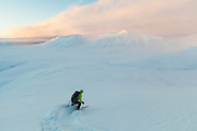 Nate Stevens skis down Hallwylfjellet, Svalbard at sunset.