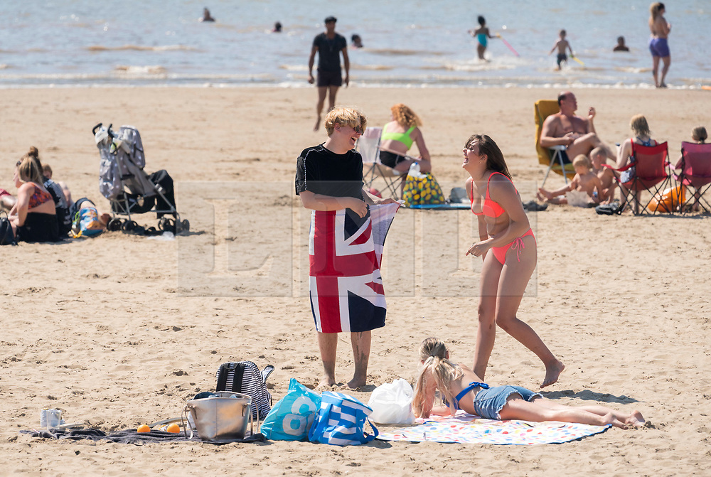 © Licensed to London News Pictures; 02/06/2020; Weston-super-Mare, UK. Two people with a union jack towel are seen at the beach. People at the beach after some lockdown restrictions due to the coronavirus covid-19 pandemic have been lifted by the UK Government. People can spend as long outdoors as they want and can meet in groups of up to six people from different households as long as they maintain social distancing of 2m or more. Photo credit: Simon Chapman/LNP.