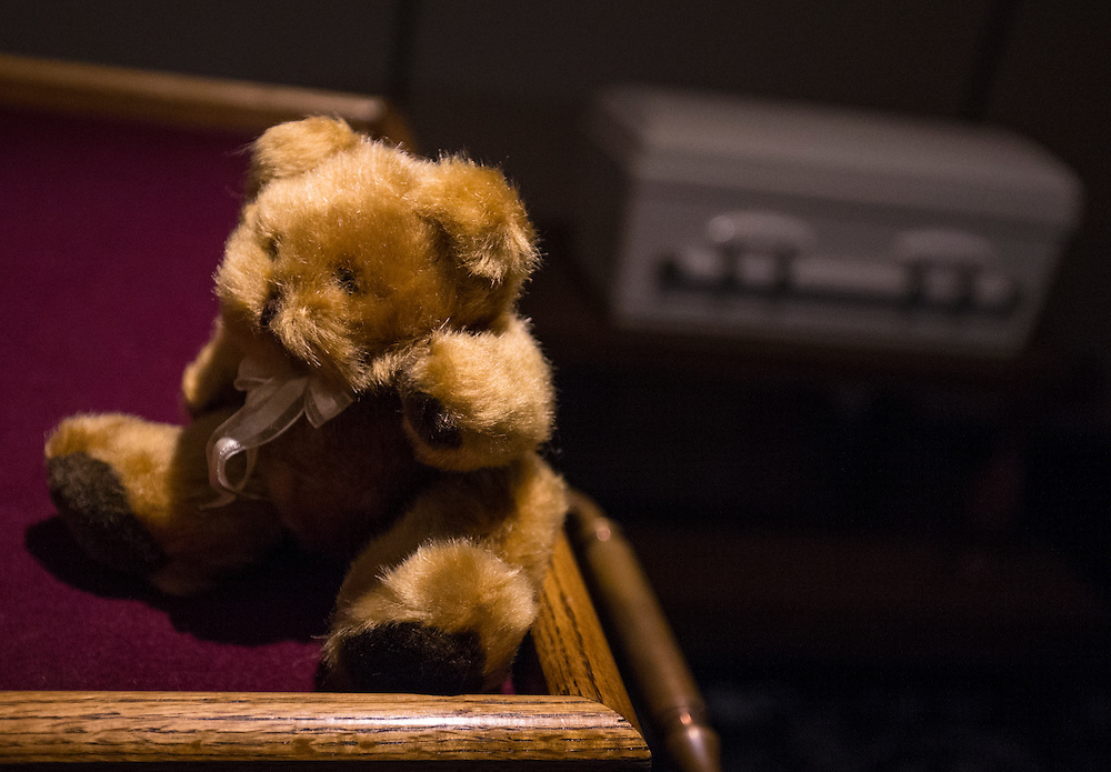 """A teddy bear sits on a table next to the casket containing the remains of an abandoned newborn baby in preparation for funeral and burial services at Glueckert Funeral Home in Arlington Heights, Illinois, United States, June 19, 2015. More than a year after he was found dead in a plastic shopping bag on a Chicago sidewalk, the baby boy was buried by a non-profit group """"Rest in His Arms"""" after being abandoned by his teenage mother, who is charged with murder.  REUTERS/Jim Young"""