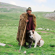 Portrait of Costica, a shepherd with his dog at his sheepfold on the Urdele pass in the remote Carpathian Mountains. He is wearing a traditional sheepskin cloak particular to shepherds in that region.
