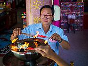 """22 AUGUST 2017 - BANGKOK, THAILAND: A man lights incense and prayer candles before praying on the first day of Hungry Ghost Month at the Poh Teck Tung Shrine in Bangkok's Chinatown. The seventh lunar month (August - September) is when many Chinese believe Hell's gate will open to allow spirits to roam freely in the human world. Many households and temples hold prayer ceremonies throughout the month-long Hungry Ghost Festival (Phor Thor) to appease the spirits. During the festival, believers will also worship the Tai Su Yeah (King of Hades) in the form of paper effigies which will be """"sent back"""" to hell after the effigies are burnt.      PHOTO BY JACK KURTZ"""