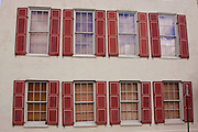 Row of identical windows along Rainbow Row in the historic Battery section of Charleston, South Carolina.