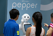 Children interact with Softbank's humanoid consumer Robot, Pepper on display at the Softbank Store Omotesando, Tokyo, Japan. Friday June 13th 2014. At the end of June 2021 the Softbank company announced it was cutting jobs in its global robotics business and had stopped production of the Pepper robot.