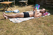 Young man sunbathing lying down on garden rug reading an academic book summer sunshine, UK