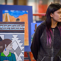 Finalist Lelahneigh Mitchell stands next to her piece during the Brea Foley Portrait Competition at the Navajo Nation Museum in Window Rock Friday.