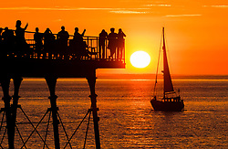 © Licensed to London News Pictures. 28/06/2018. Aberystwyth, UK. A yacht sails through a  spectacular sunset over Cardigan Bay , Aberystwyth, at the end of a day of record breaking temperatures across the UK. Photo credit: Keith Morris/LNP