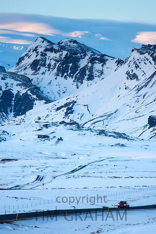 Car motoring on Main Road in Southern Iceland with Katla volcano behind under glacier ice cap in Katla Geopark near Vik, Iceland