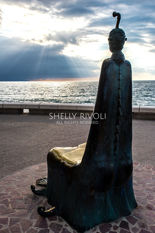 A single chair throne sculpture with head and feet looks out at the Bay of Banderas with sun bursting through clouds on the Puerto Vallarta malecon or boardwalk.