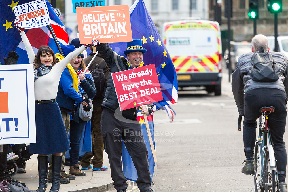 Pro-Leave protester Lydia, originally an immigrant from Peru and now a British citizen, tries to attract hoots from passing cars outside the Houses of Parliament in London whilst Steve Bray, Leader of SODEM (Stand of Defiance European Movement) jumps in front with his pro-Remain placards. London, January 14 2019.