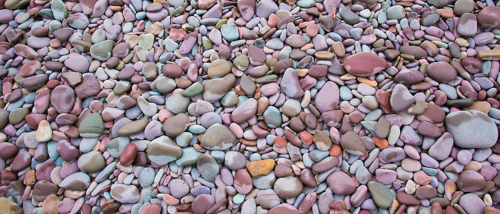 Rain on pebbles makes a splash of colour as rain starts to fall on Bossington Beach, Somerset, UK