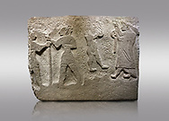 Alaca Hoyuk Hittite monumental relief sculpted orthostat stone panel. Andesite, Alaca, Corum, 1399 - 1301 B.C. Anatolian Civilizations Museum, Ankara, Turkey<br /> <br /> The rightmost figure wears a long coat and tailed dress. With both hands, he holds a sceptre with a ring in the middle. This item is thought to be a cult object in Assyria reliefs. The pointed and twisted tips of his shoes also show that he is in a high rank.  <br /> <br /> Against a brown gray background. .<br />  <br /> If you prefer to buy from our ALAMY STOCK LIBRARY page at https://www.alamy.com/portfolio/paul-williams-funkystock/hittite-art-antiquities.html . Type - Aalca Hoyuk - in LOWER SEARCH WITHIN GALLERY box. Refine search by adding background colour, place, museum etc..<br /> <br /> Visit our HITTITE PHOTO COLLECTIONS for more photos to download or buy as wall art prints https://funkystock.photoshelter.com/gallery-collection/The-Hittites-Art-Artefacts-Antiquities-Historic-Sites-Pictures-Images-of/C0000NUBSMhSc3Oo