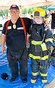 Firefighter with boy age 11 dressed in rescue outfit at demonstration. Aquatennial Beach Bash Minneapolis Minnesota USA