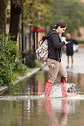 A women texts as she walks through floodwater across Church Street in the historic district as Hurricane Joaquin brings heavy rain, flooding and strong winds as it passes offshore October 4, 2015 in Charleston, South Carolina.