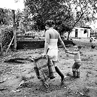 A mother and daughter set off to pick coca leaves on a small cooperative plantaion on the banks of the Rio Putumayo.<br />