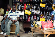 Men sit by a street stall offering bags for sale in central Accra, Ghana on Tuesday June 16, 2009.