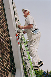 Painter and decorator climbing ladder against exterior of house,