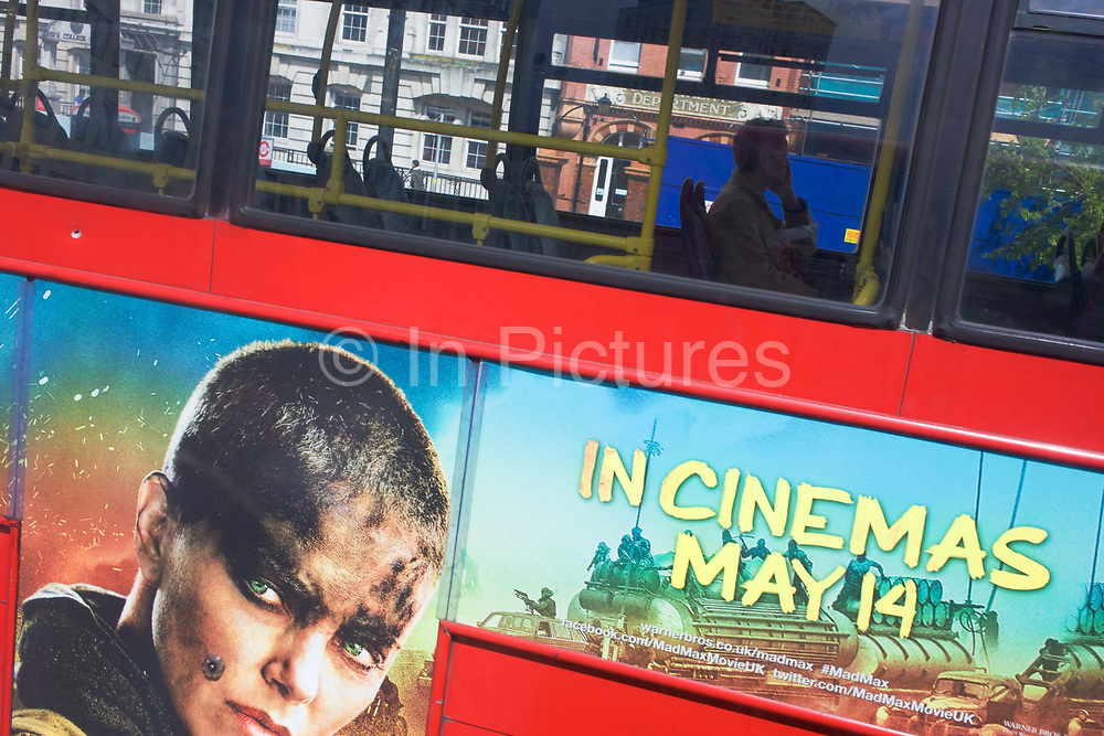 Lone man on central London bus and film advertising. The passenger rides on the toip top deck of the bus, distant in thought as he travels southwards in the capital. On the side of the vehicle we see the face of Charlize Theron in her role as Imperator Furiosa, a character in the remake of dystopian fantasy film Mad Max.