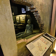 "Part of the original wall has been cut away and replaced with glass so that visitors can see inside the small, dark cells along death rwo at Hoa Lo Prison in Hanoi. A plastic dummy illustates the conditions. Better known in the West as ""the Hanoi Hilton"", part of the prison has been preserved as a museum."