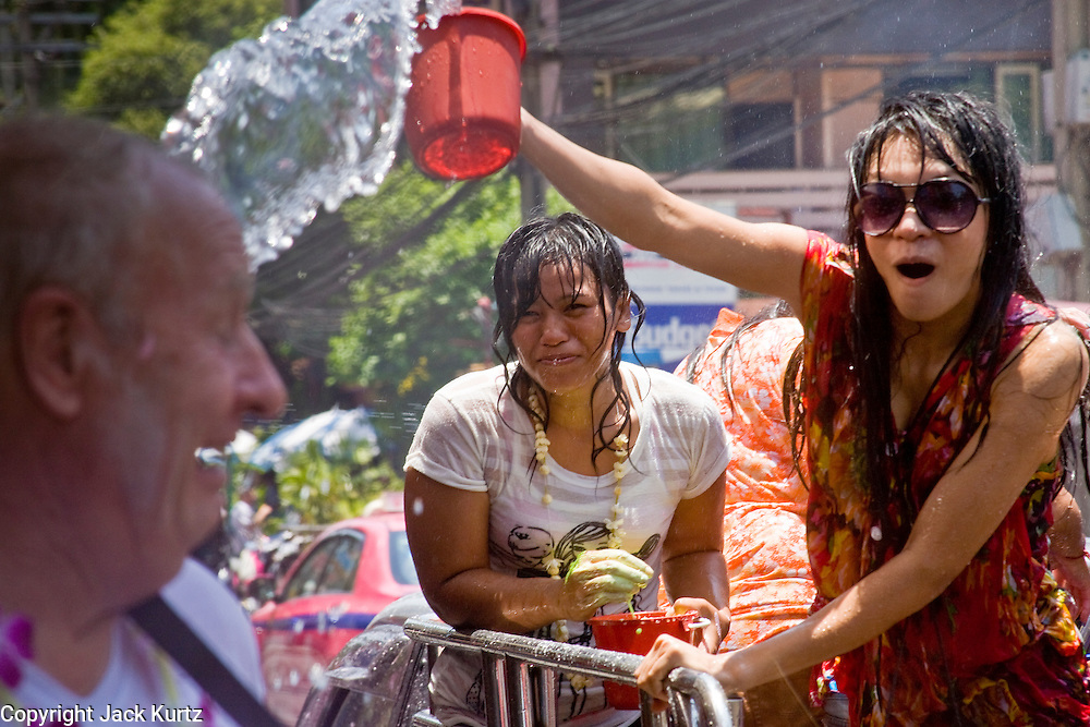 """Apr. 13, 2010 - Bangkok, Thailand: Thai women throw water at a tourist during Songkran festivities on a soi off of Sukhumvit Rd in Bangkok Tuesday. Songkran is the Thai New Year's holiday, celebrated from April 13 - 15. This year's official celebrations have been cancelled because of the Red Shirt protests but Thais are still marking the holiday. It's one of the most popular holidays in Thailand. Songkran originally was celebrated only in the north of Thailand, and was adapted from the Indian Holi festival. Except the Thais throw water instead of colored powder. The throwing of water originated as a way to pay respect to people, by capturing the water after it had been poured over the Buddhas for cleansing and then using this """"blessed"""" water to give good fortune to elders and family by gently pouring it on the shoulder. Among young people the holiday evolved to include dousing strangers with water to relieve the heat, since April is the hottest month in Thailand (temperatures can rise to over 100°F or 40°C on some days). This has further evolved into water fights and splashing water over people riding in vehicles. The water is meant as a symbol of washing all of the bad away and is sometimes filled with fragrant herbs when celebrated in the traditional manner. Photo by Jack Kurtz"""