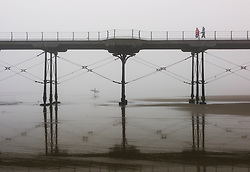 © Licensed to London News Pictures. <br /> 08/05/2016. <br /> Saltburn by the Sea, UK.  <br /> <br /> Two people walk along the pier as a surfer heads into the water as heavy fog shrouds the coastline at Saltburn by the Sea in North Yorkshire as much of the country enjoys the hottest temperatures of the year so far.<br /> <br /> Photo credit: Ian Forsyth/LNP