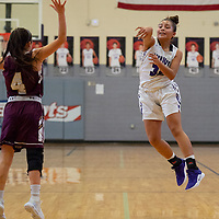 Fetisha Johnson (32) of Miyamura passes at the top of the key as Katrina Lueras (4) of Belen tries to defend in Gallup on Saturday. The Lady Patriots won 63-34.