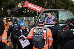 A farmer in a telehandler asks National Eviction Team bailiffs working on behalf of HS2 Ltd for clarification as to why they are erecting a fence across his field during the eviction of anti-HS2 activists from a wildlife protection camp in ancient woodland at Jones' Hill Wood alongside the field on 1 October 2020 in Aylesbury Vale, United Kingdom. Around 40 environmental activists and local residents, some of whom living in makeshift tree houses about 60 feet above the ground, were present during the evictions at Jones' Hill Wood which had served as one of several protest camps set up along the route of the £106bn HS2 high-speed rail link in order to resist the controversial infrastructure project.