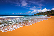 Surf and sand on Secret Beach (Kauapea Beach), Kilauea Lighthouse visible, Kauai, Hawaii USA