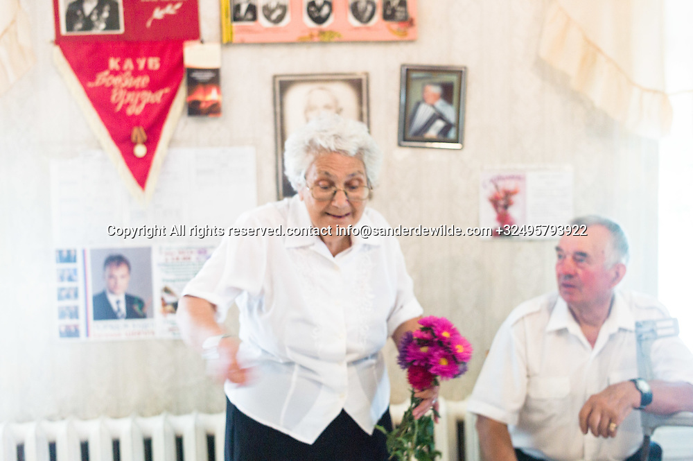 20150829  Moldova, Transnistria,Pridnestrovian Moldavian Republic (PMR) Dubushari. An old femal eVeterans got flowers after singing old soviet songs in the soviet clubhouse in Dubushari.The walls are decorated with old pictures and soviet signs, all singers are dressed in white.