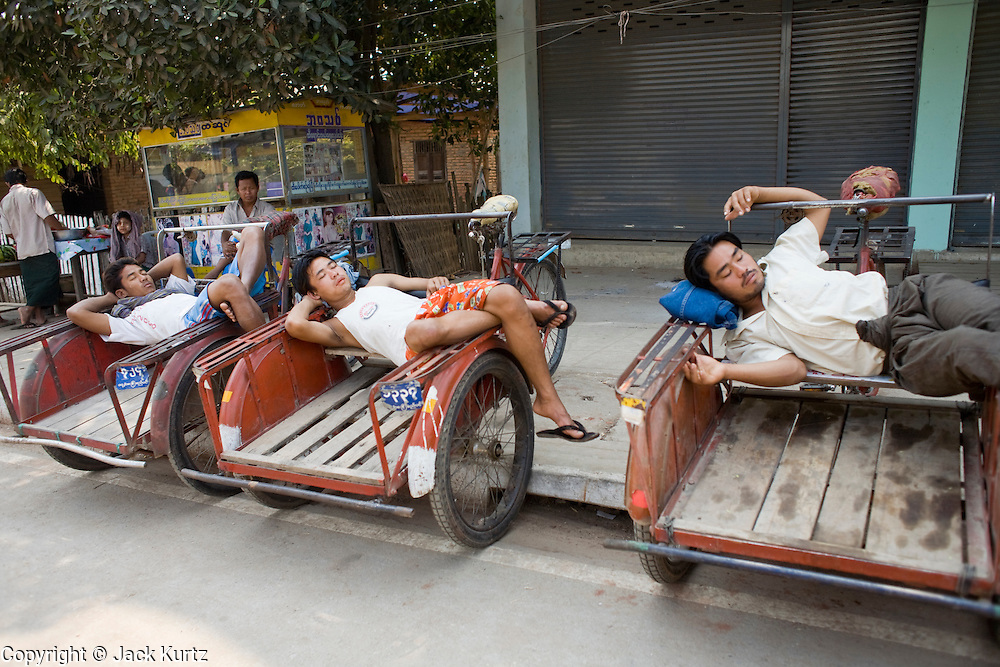 26 FEBRUARY 2008 -- MYAWADDY, MYANMAR: Rickshaw drivers nap while waiting for fares in Myawaddy, Myanmar (Burma). Myawaddy is just across the Moei River from Mae Sot, Thailand and is one of Myanmar's leading land ports for goods going to and coming from Thailand. Most of the businesses in the town are geared towards trade, both legal and illegal, with Thailand. Human rights activists from Myanmar maintain that the Burmese government controls the drug smuggling trade between the two countries and that most illegal drugs made in Myanmar are shipped into Thailand from Myawaddy.   Photo by Jack Kurtz