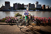 TOKYO, JAPAN, 5 MAY - Sumida gawa - A man with a bicycle wear a white mask and a white cap, that could not permit us to know is identity. May 2012