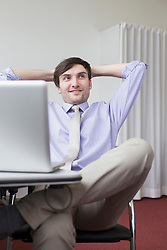 Businessman sitting in office, smiling