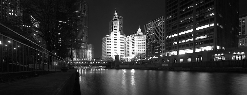 The Wrigley building is seen at night along the Chicago River.