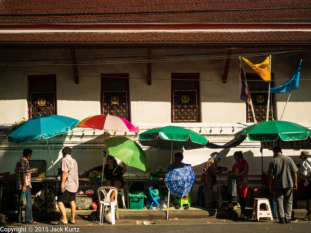29 NOVEMBER 2015 - BANGKOK, THAILAND:  Vendors in the Amulet Market on Maharat Road on the last day the market was open. Hundreds of vendors used to sell amulets and Buddhist religious paraphernalia to people in the Amulet Market, a popular tourist attraction along Maharat Road north of the Grand Palace near Wat Maharat in Bangkok. Bangkok municipal officials announced that they are closing the market and forcing vendors to relocate to an area about one hour outside of Bangkok. The closing of the amulet market is the latest in a series of municipal efforts to close and evict street vendors and markets from areas that have potential for redevelopment. The street vendors were evicted from the area on Sunday, Nov. 29.      PHOTO BY JACK KURTZ