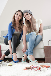 Portrait of two young female friends sitting side by side on couch at home trying on high heels