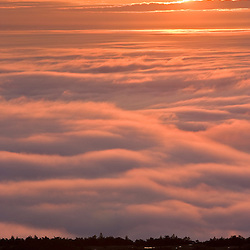 The sun rises above the fog as seen from the summit of Cadillac Mountain in Maine's Acadia National Park.
