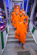 20 OCTOBER 2012 - BANGKOK, THAILAND: Buddhist monks file out of the Phrom Prong Skytrain station in Bangkok to attend an alms giving ceremony. More than 2,600 Buddhist Monks from across Bangkok and thousands of devout Thai Buddhists attended the mass alms giving ceremony in Benjasiri Park in Bangkok Saturday morning. The ceremony was to raise food and cash donations for Buddhist temples in Thailand's violence plagued southern provinces. Because of an ongoing long running insurgency by Muslim separatists many Buddhist monks in Pattani, Narathiwat and Yala, Thailand's three Muslim majority provinces, can't leave their temples without military escorts. Monks have been targeted by Muslim extremists because, in the view of the extremists, they represent the Thai state.     PHOTO BY JACK KURTZ