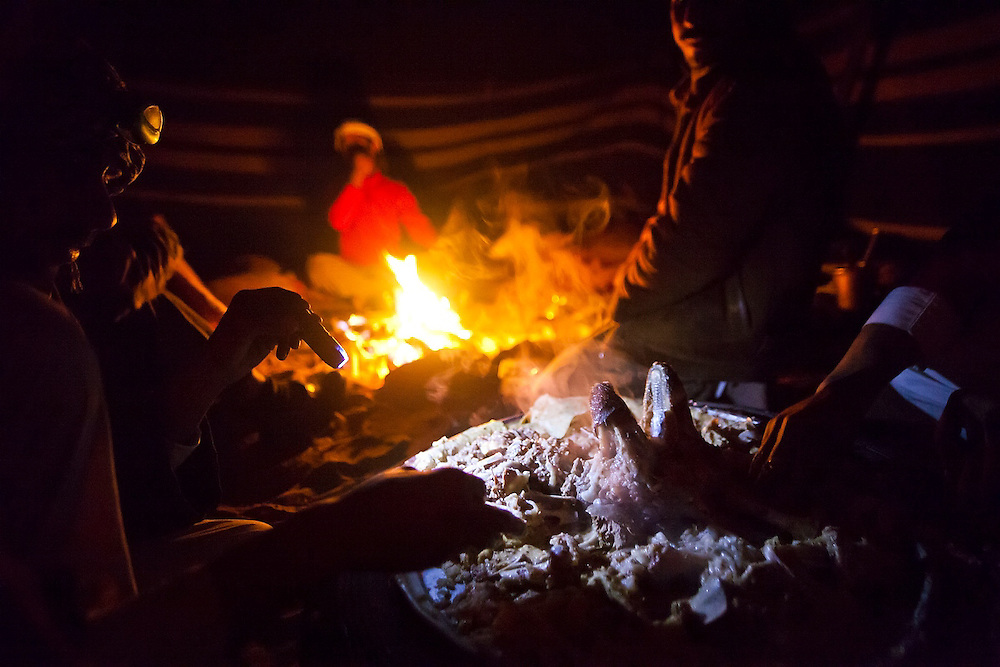 Bedouin men eat by flashlight with their hands from a platter of mansaf, a local delicacy of goat roasted in yogurt, at a Bedouin encampment in Wadi Rum, Jordan.