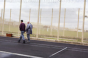 Two prisoners walking around the excerise yard. Beaufort House, a skill development unit for enhanced prisoners. Part of HMP/YOI Portland, a resettlement prison with a capacity for 530 prisoners.Dorset, United Kingdom.