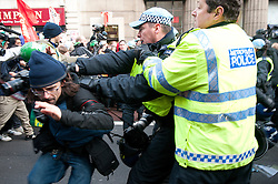 © under license to London News Pictures.  09/12/2010. Police grab a journalist as students run down the street in London during a chaotic start to the fourth march against the proposed rise in tuition fees in as many weeks. Photo credit should read Michael Graae/London News Pictures