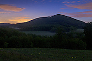 Salisbury Mills, New York - Fireflies shine in a field in the foreground of this evening view of Schunnemunk Mountain and the Moodna Viaduct on May 24, 2014.