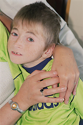 Young boy with cerebral palsy waiting for Baclofen Implant Pump being held by mother on Children's ward of hospital,