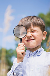 Little boy looking through a magnifying glass in the countryside, Bavaria, Germany