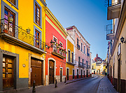 Street in Guanajuato, Mexico<br /> ------<br /> Guanajuato is a city and municipality in central Mexico and the capital of the state of the same name. It is part of the macroregion of Bajío. It is in a narrow valley, which makes its streets narrow and winding. Most are alleys that cars cannot pass through, and some are long sets of stairs up the mountainsides. Many of the city's thoroughfares are partially or fully underground. The historic center has numerous small plazas and colonial-era mansions, churches and civil constructions built using pink or green sandstone.<br /> <br /> The origin and growth of Guanajuato resulted from the discovery of minerals in the mountains surrounding it. The mines were so rich that the city was one of the most influential during the colonial period. One of the mines, La Valenciana, accounted for two-thirds of the world's silver production at the height of its production.<br /> <br /> The city is home to the Mummy Museum, which contains naturally mummified bodies that were found in the municipal cemetery between the mid 19th and 20th centuries. It is also home to the Festival Internacional Cervantino, which invites artists and performers from all over the world as well as Mexico. Guanajuato was the site of the first battle of the Mexican War of Independence between insurgent and royalist troops at the Alhóndiga de Granaditas. The city was named a World Heritage Site in 1988. in Guanajuato, Mexico<br /> ------<br /> Guanajuato is a city and municipality in central Mexico and the capital of the state of the same name. It is part of the macroregion of Bajío. It is in a narrow valley, which makes its streets narrow and winding. Most are alleys that cars cannot pass through, and some are long sets of stairs up the mountainsides. Many of the city's thoroughfares are partially or fully underground. The historic center has numerous small plazas and colonial-era mansions, churches and civil constructions built using pink or green sandstone.<b