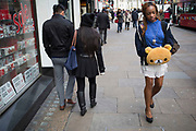 Woman with a bear shaped hand warmer walks through London, UK.