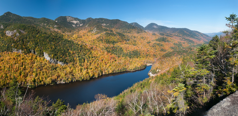 Adirondack Mountain Reserve, NY.<br /> The perch is Indian Head.  I've done the long slog from way down at the beginning of this valley to the Fish Hawk Cliffs, about half a mile behind me, and the ridge trail to here. Five peaks of the Great Range loom across Lower Ausable Lake, two more above and behind me. I can pick out the watercourses I know so well from up here, the arteries and veins that move the life blood from the extremes at the mountain tops to the heart of the earth, deep into the gorges that close in, and pulse with life and power.  It all drains earthward...weather, water, rock, wood, even color--spreading out in alluvial fans on the valley floor, all of it absorbed into the blackness of the lake.  I sit awhile, eat something, and think about what has been drained out of me.  The pool beneath my feet would fill with the faith, and hope, and love that has been weathered and eroded by human nature.  Such a fool to think I could have those things forever, to think my human bonds could be stronger than the bonds that hold this piece of earth together.  Every mortal storm depletes us.  And if I am not drained yet, it is only because I have so much fartherto go, to return.