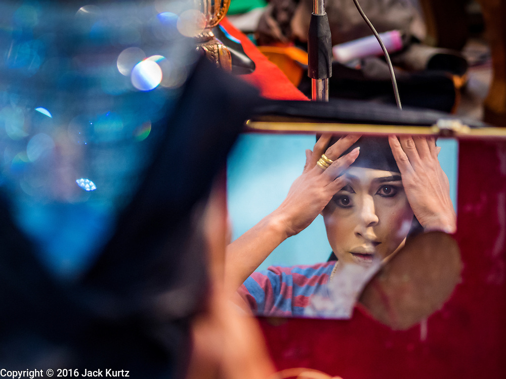 """30 JANUARY 2016 - NONTHABURI, NONTHABURI, THAILAND: A performer looks into a broken mirror while gets ready for a """"likay"""" show at Wat Bua Khwan in Nonthaburi, north of Bangkok. Likay is a form of popular folk theatre that includes exposition, singing and dancing in Thailand. It uses a combination of extravagant costumes and minimally equipped stages. Intentionally vague storylines means performances rely on actors' skills of improvisation. Like better the known Chinese Opera, which it resembles, Likay is performed mostly at temple fairs and privately sponsored events, especially in rural areas. Likay operas are televised and there is a market for bootleg likay videos and live performance of likay is becoming more rare.     PHOTO BY JACK KURTZ"""