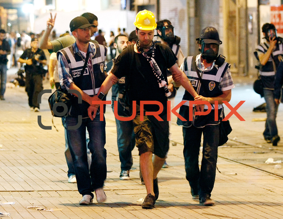 A protester is led away by police officers during an anti-government protest at Taksim Square in Istanbul, Turkey, 06 July 2013. Turkish police used tear gas and water cannon against peaceful protesters on Istanbul's Taksim Square on 06 July after the city's governor banned a planned evening demonstration. Photo by AYKUT AKICI/TURKPIX