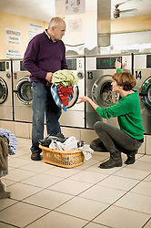 Young woman is helping to senior man in laundry
